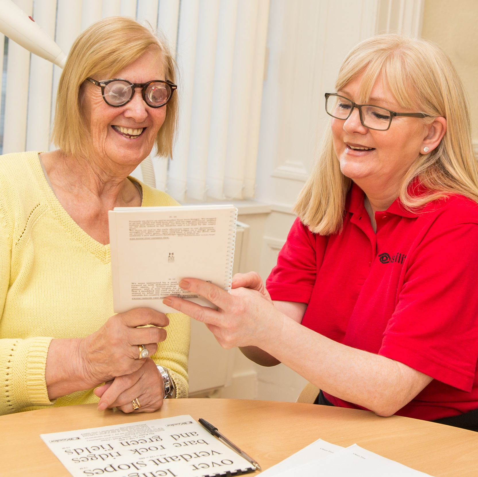 Jessie reading a pad of paper with hyper-ocular glasses on, while Liz the tutor smiles at her