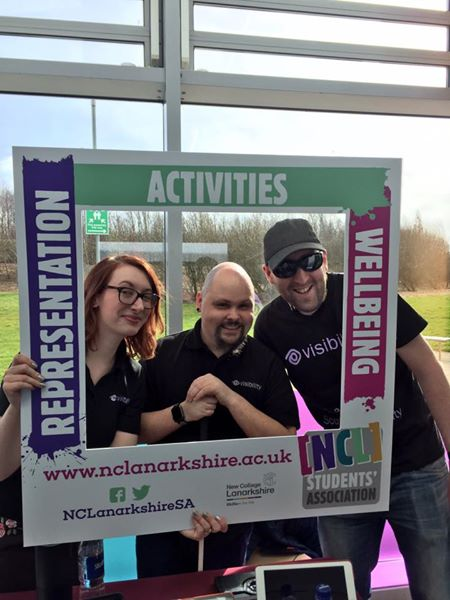 photo of Sarah, Fraser and Graham holding a frame around their faces which advertises the north lanarkshire students association
