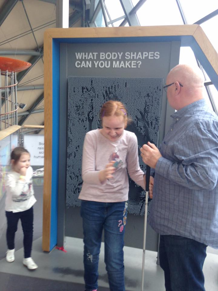 """picture shows young girl with cane using an exhibit called """"what body shapes can you make?"""" where you stand against a wall of soft tactile prongs and make shapes"""