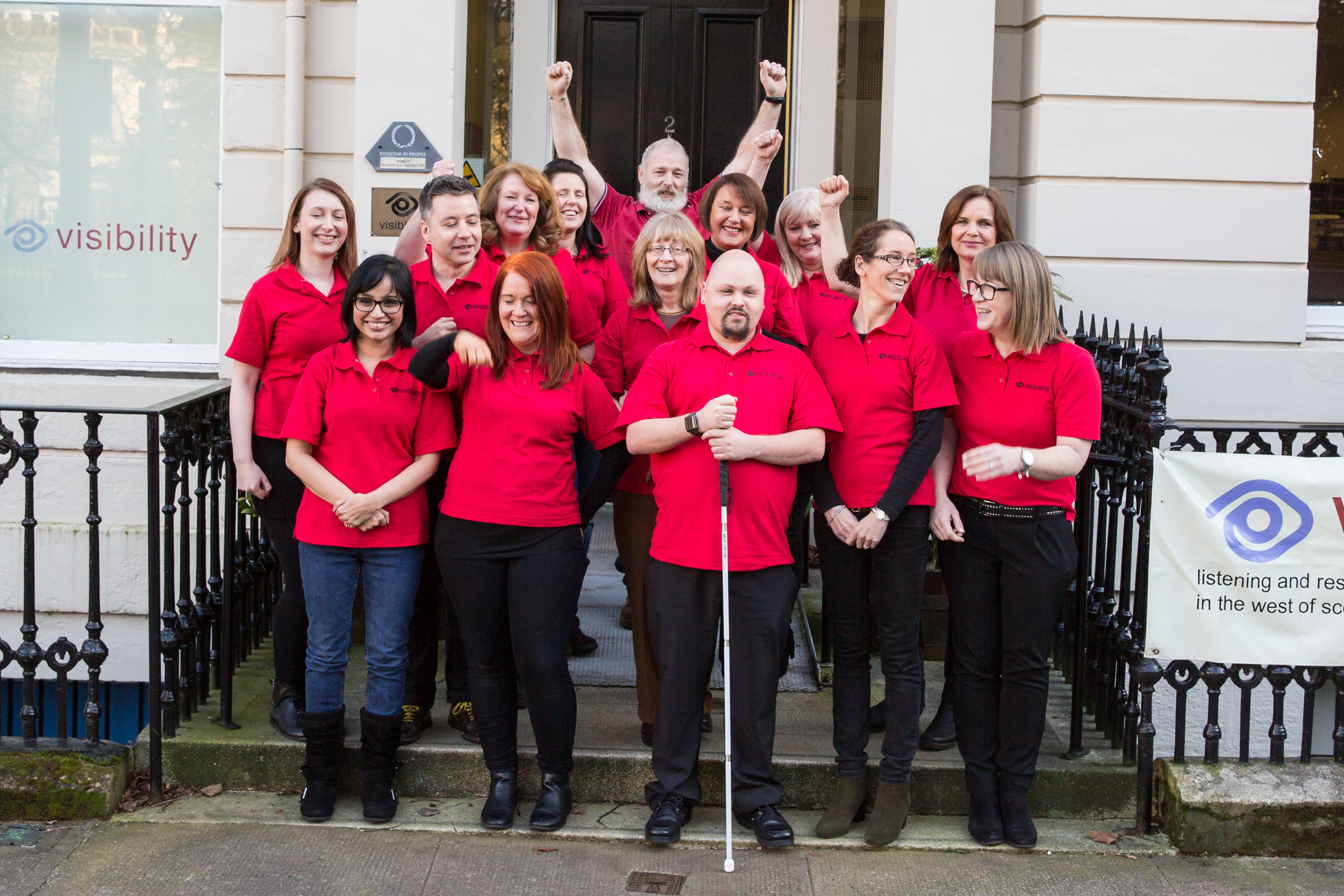 a group picture of staff at Visibility, all wearing red polo shirts, standing outside the entrance to the Glasgow office