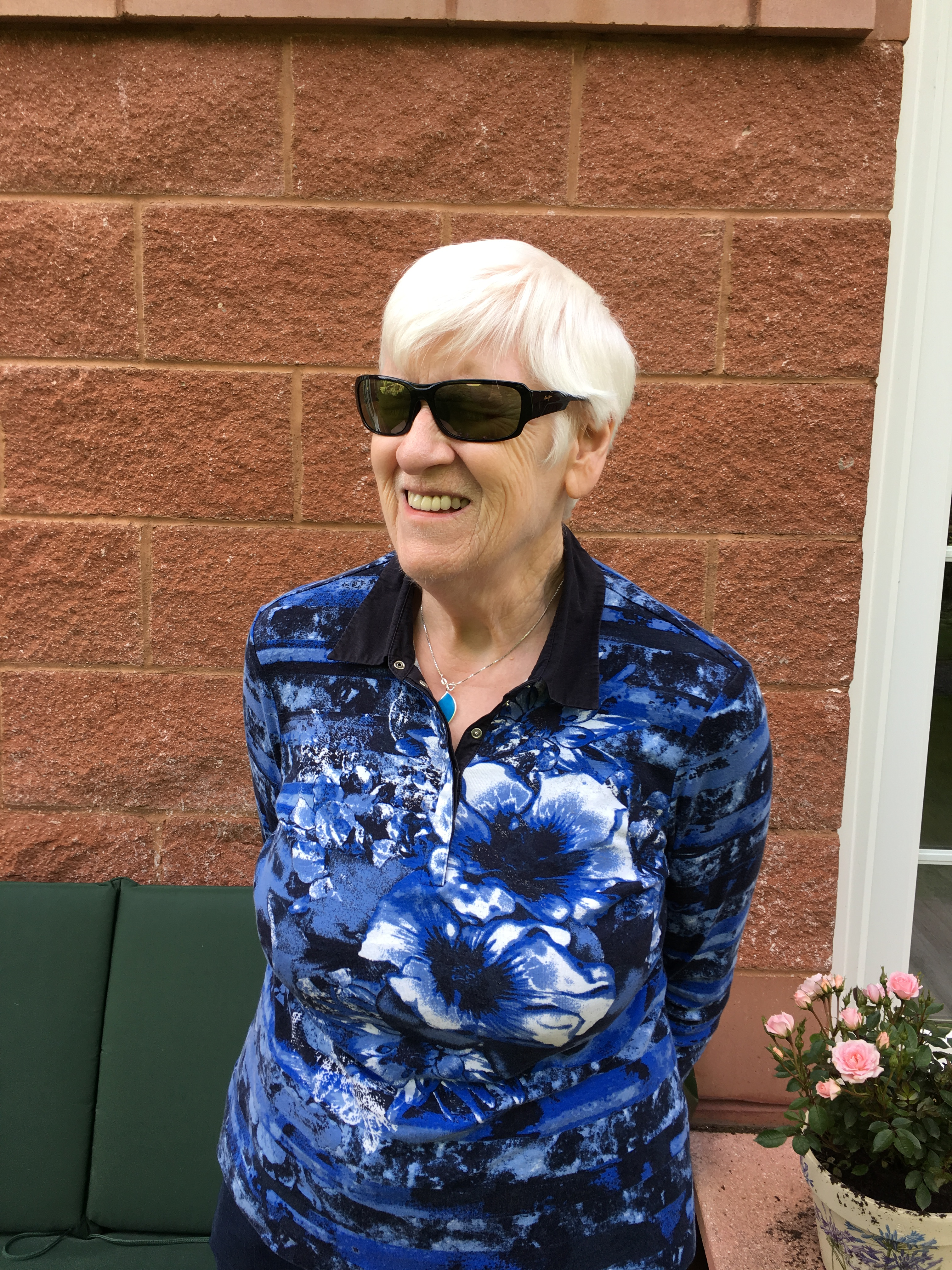 Liz, a lady with white hair and dark glasses smiling and wearing a blue blouse