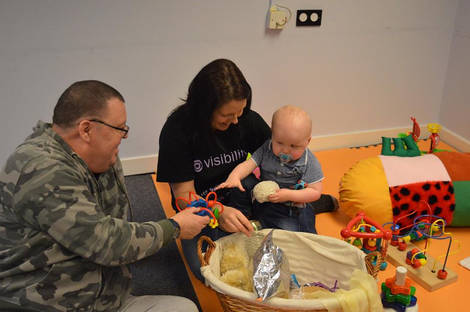 little boy playing with toys and sitting with his dad and staff member Aoife
