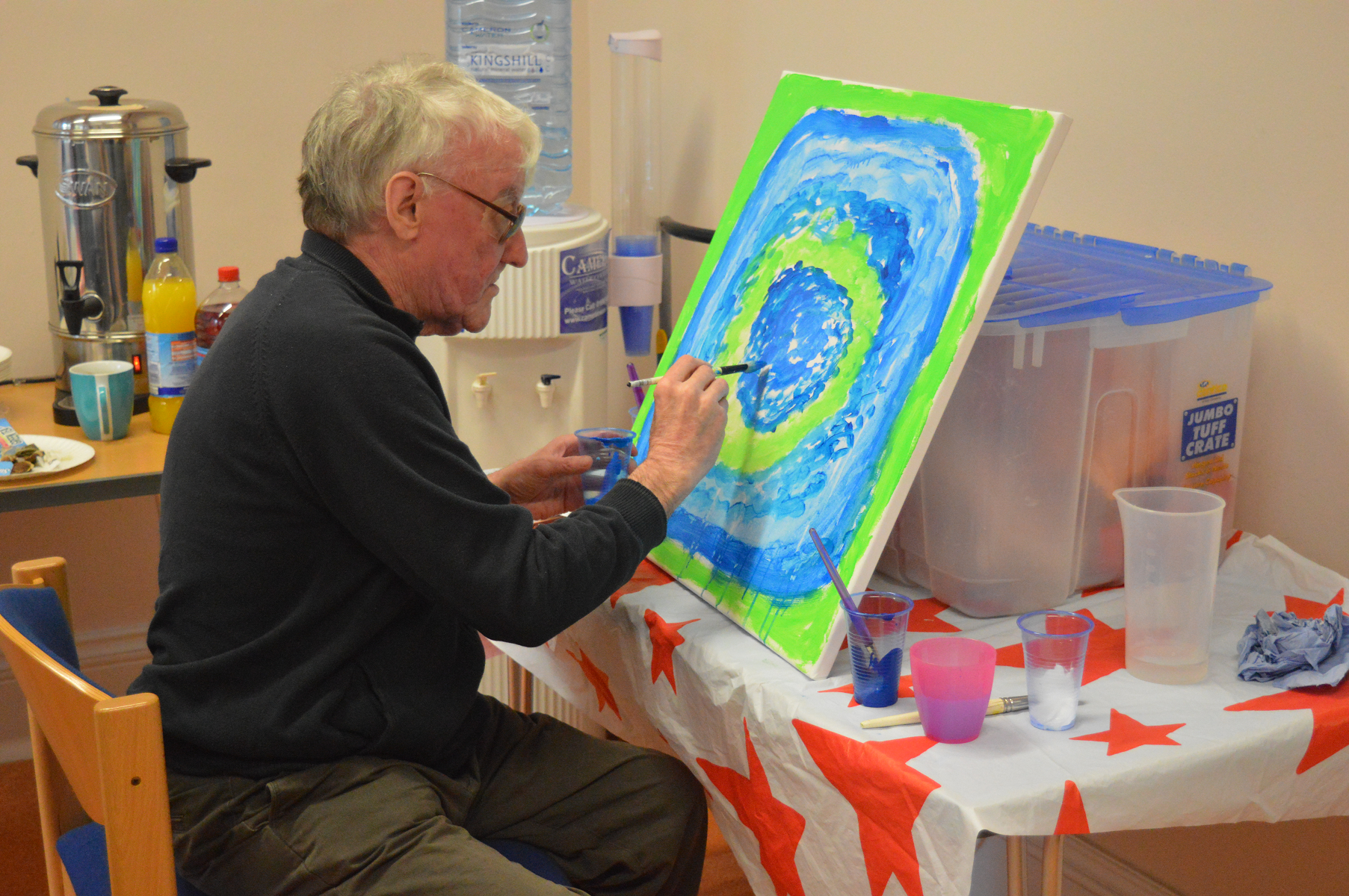 A man with glasses painting a canvas with green and blue paint