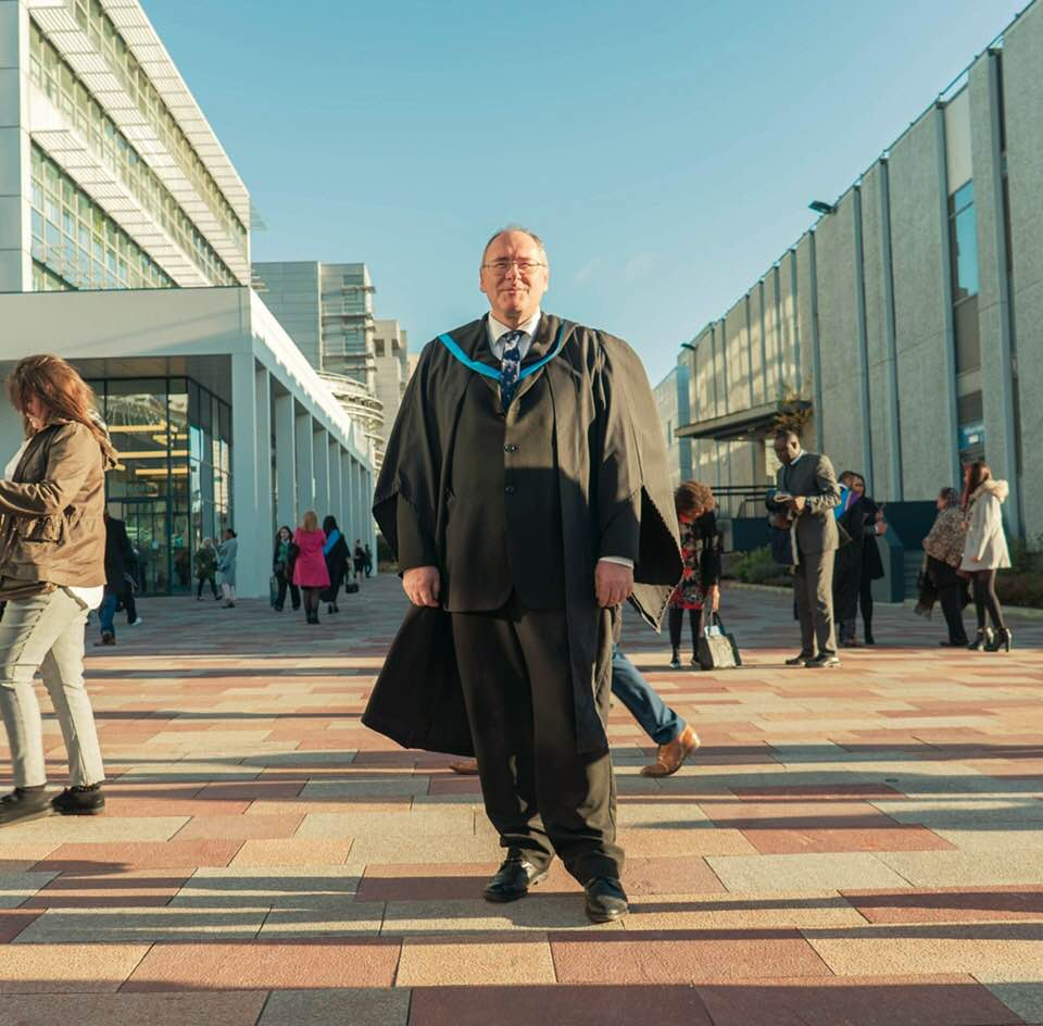 David, a man wearing glasses and a graduation robe, standing outside Glasgow Caledonian University