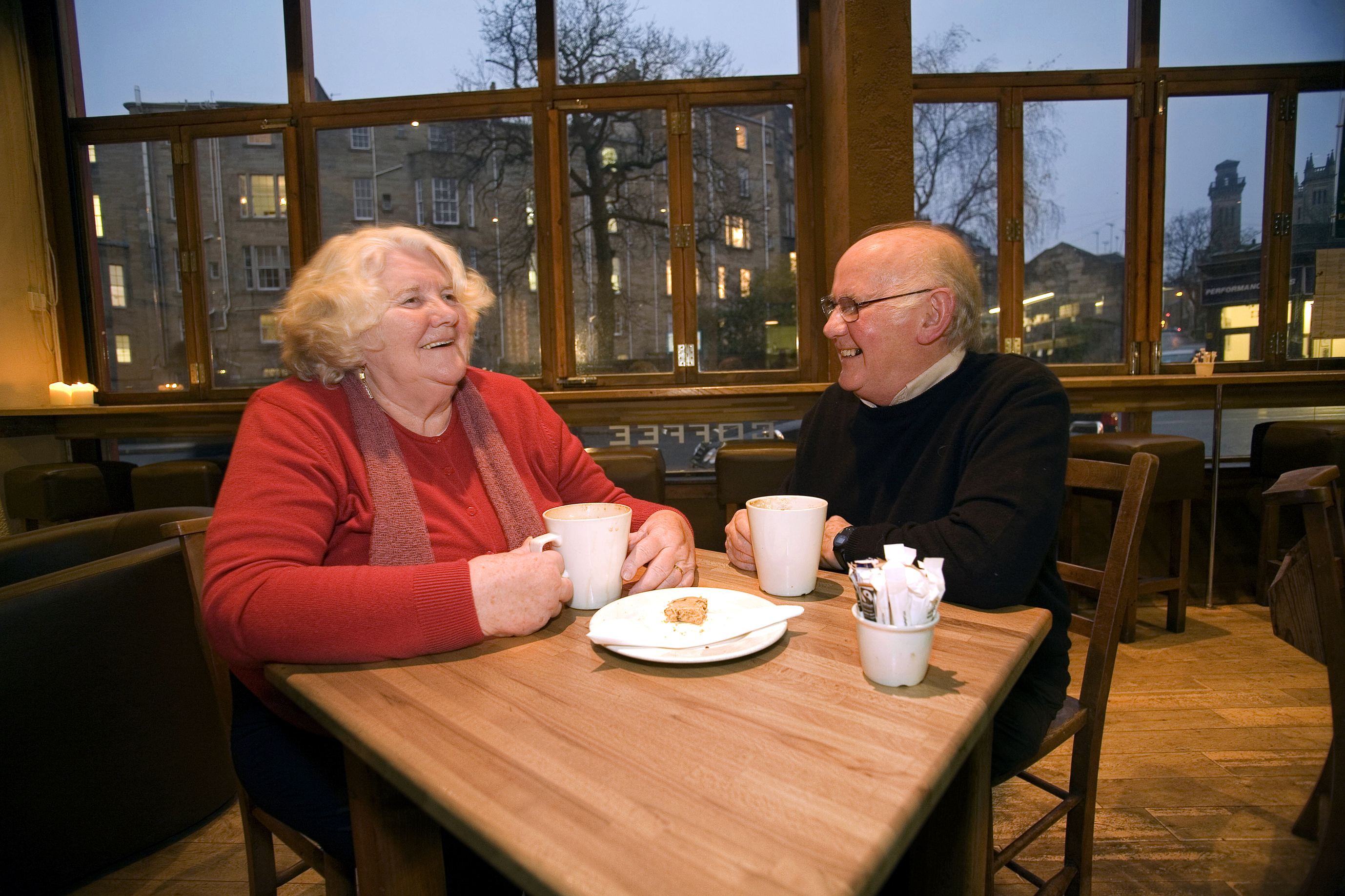 A woman and a man sitting in a cafe smiling whilst having a chat and a cup of tea each