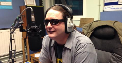 David sitting behind a microphone at a mixing desk wearing dark glasses