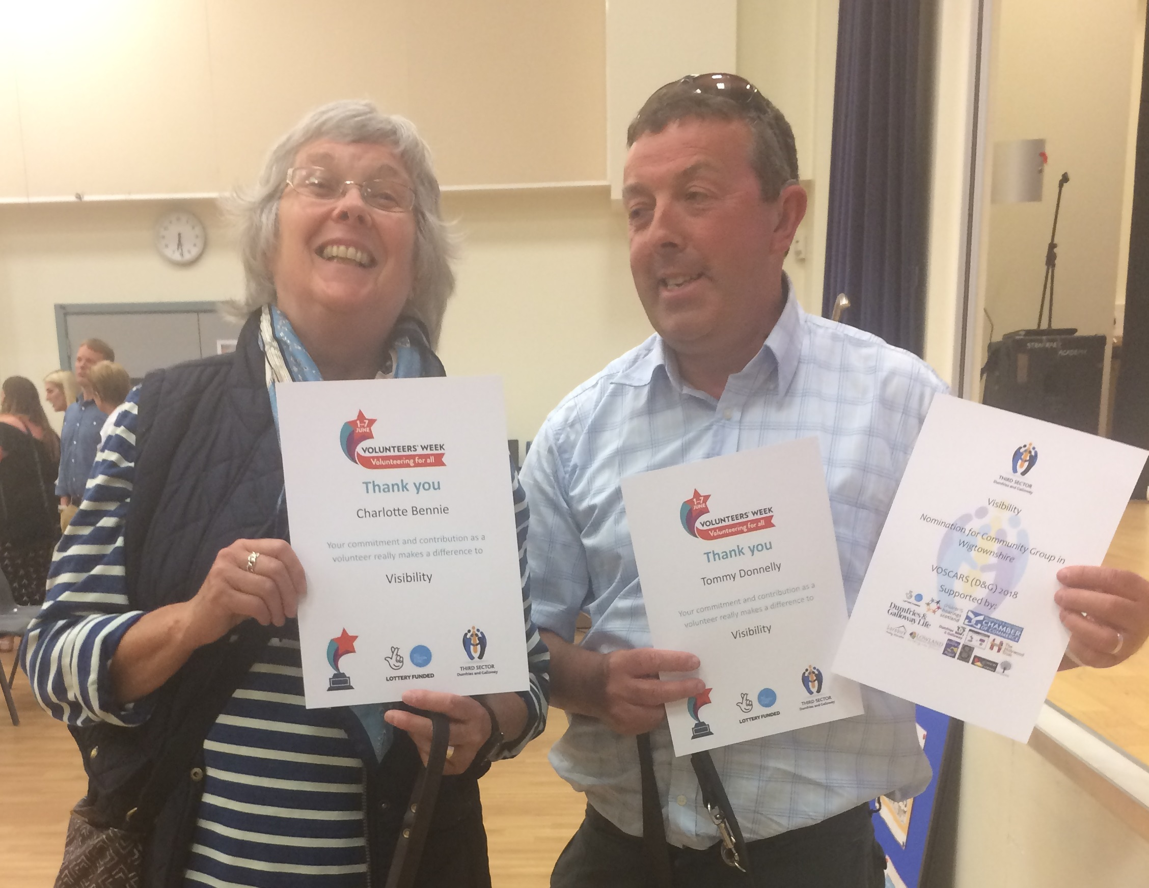 image shows Charlotte and Tommy holding their volunteer certificates and smiling