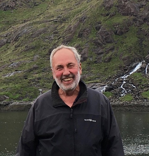 Picture shows Howard smiling, he is outdoors walking in front of a river and hills