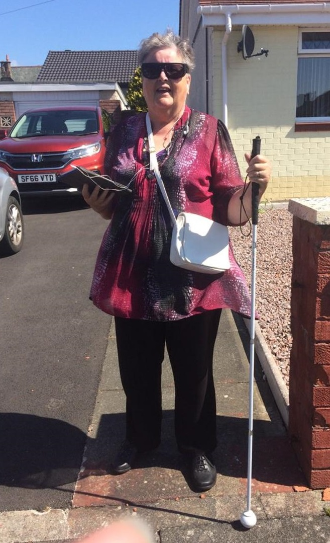 Anne stands outside a house holding a long cane in one hand and her iPad in the other hand. She is wearing dark glasses and smiling in the sunshine.