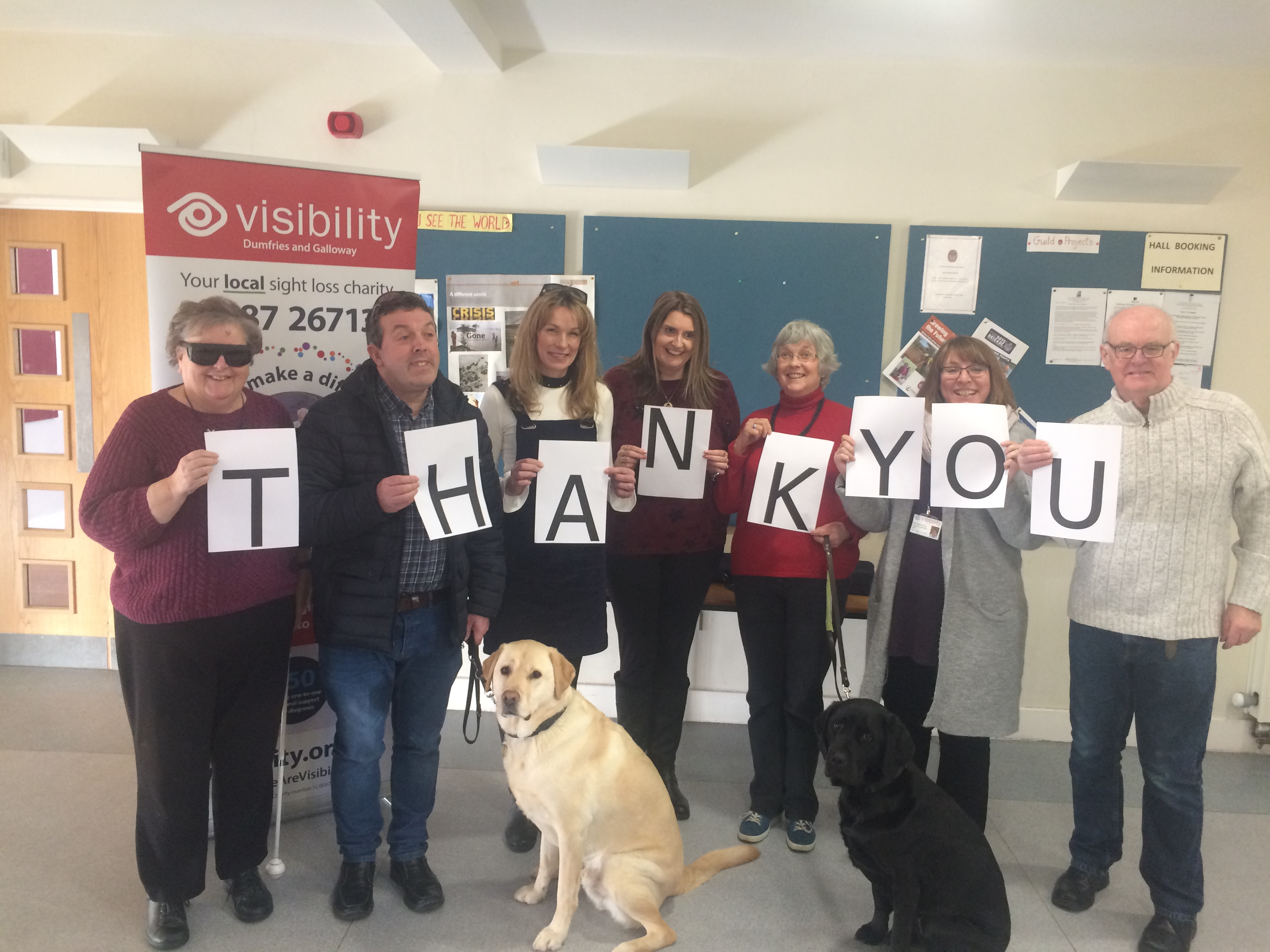 "a group of people involved in our sensory inspirer project holding up pieces of paper spelling out the word ""thank you"" and there is a guide dog sitting on the floor at the front of the group"