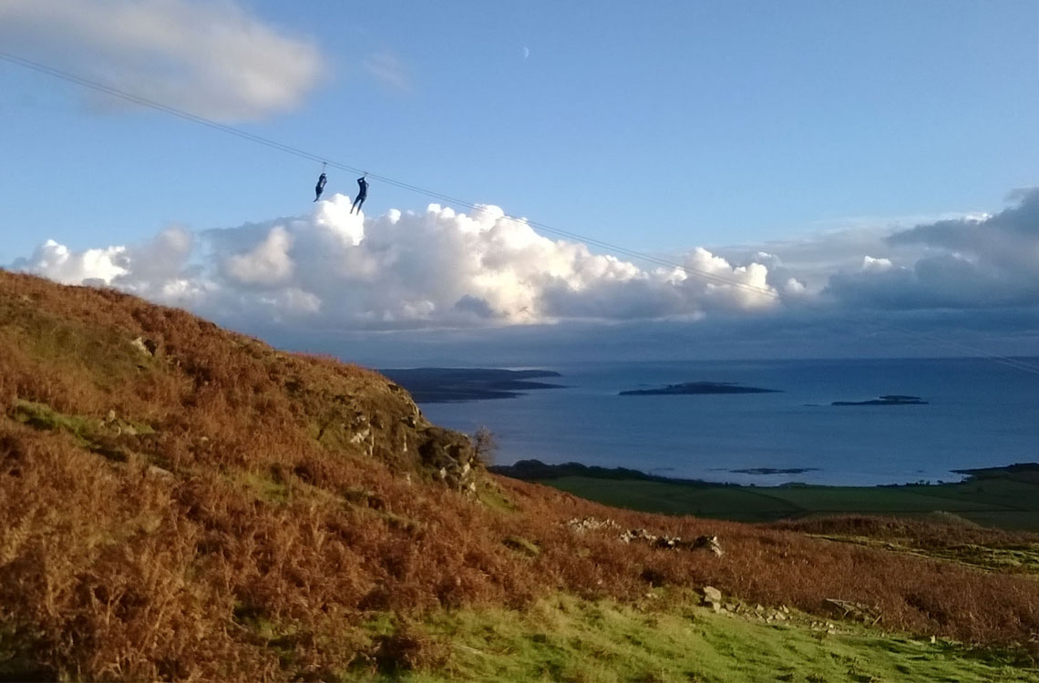 People taking the Laggan Outdoor Zipslide Challenge. The photo shows a gorse-covered hill and beautiful blue sky with the zipsliders coming through the middle of the screen.