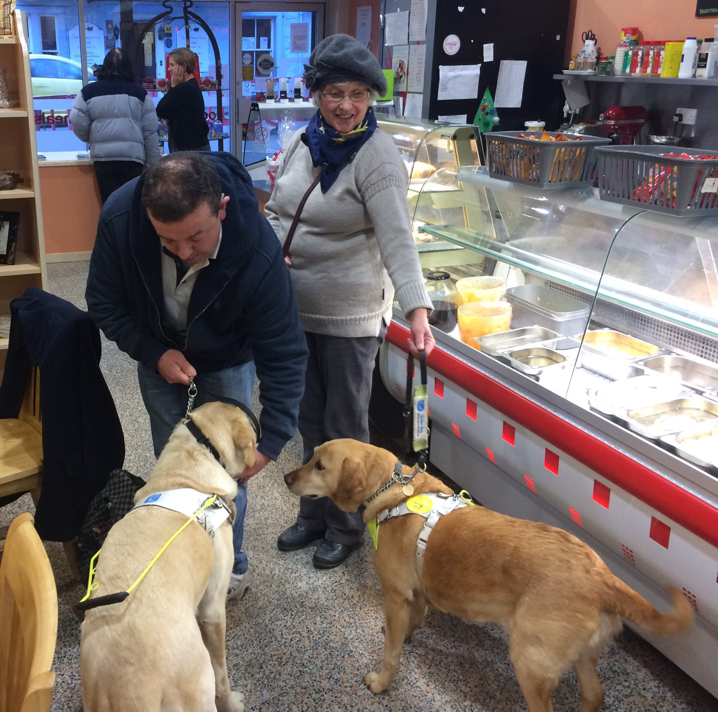 A group of people in a cafe with a guide dog