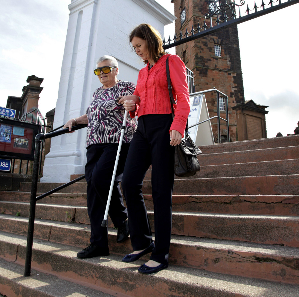 Visibility staff member helping a visually impaired woman walk down some steps outside